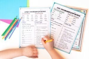 Child using spelling worksheets with colored pencils.
