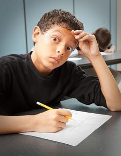 Worried student looking at camera with large eyes holding a pencil with a standardized test in front of him