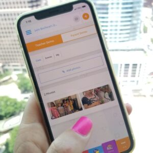 Image of a woman's hand holding a cell phone with the ClassTag App open to the Parent-Teacher communication page