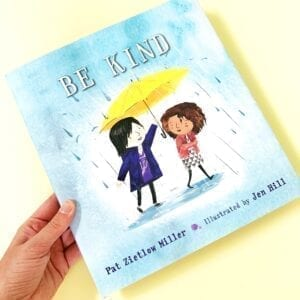 Cover of book called Be Kind showing two girls on the cover, one is holding an umbrella over the other's head and it is raining