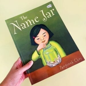 Cover of The Name Jar showing a girl putting paper into a jar on a table. The jar already has other small pieces of paper in it.