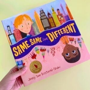 Cover of book called Same, Same but Different, showing two diverse children from different cultures with different city-scapes behind them.