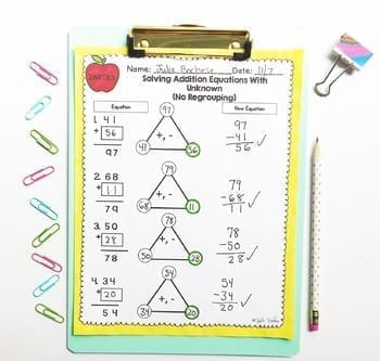 Adding Two Digit Equations (No Regrouping) Worksheet with fact triangles on a clipboard surrounded by paper clips, a binder clip, and a pencil