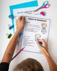 Person drawing on a types of questions anchor chart showing inferential and explicit question types