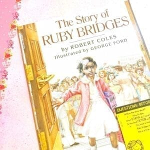 Cover of Ask and Answer Mentor Text The Story of Ruby Bridges showing image of young Ruby Bridges walking through a door and a sticky note with questions on the bottom right side of book.