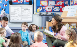 A teachers reads to her class while sitting on the floor in a circle. An open book is in her hand, and she is looking directly at a student while discussing predicting strategies with the group.
