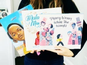 Teacher holding three mentor texts focused on character traits and character education, including book titled Mary Wears What She Wants.
